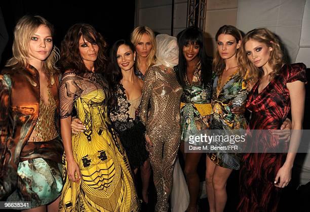 Models Sasha Pivovarova Helena Christensen Daphne Guinness and Naomi Campbell pose wearing Alexander McQueen backstage at Naomi Campbell's Fashion...