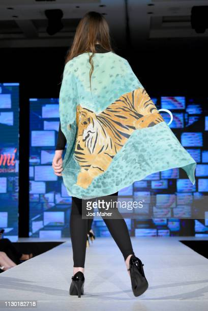 Models scarf detail walk the runway for Nadia Azumi at the House of iKons show during London Fashion Week February 2019 at the Millennium Gloucester...