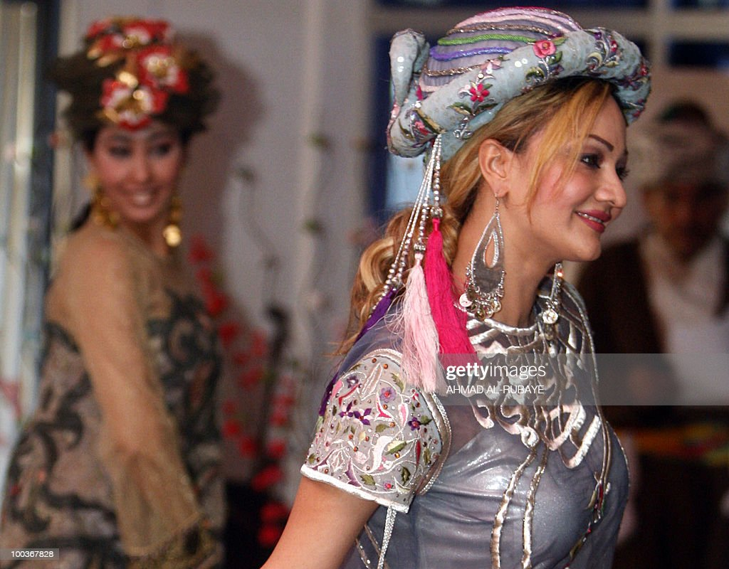 Models show off long organza dresses decorated in Arabesque designs during a fashion show at the Ministry of Culture on May 24, 2010 in Baghdad.