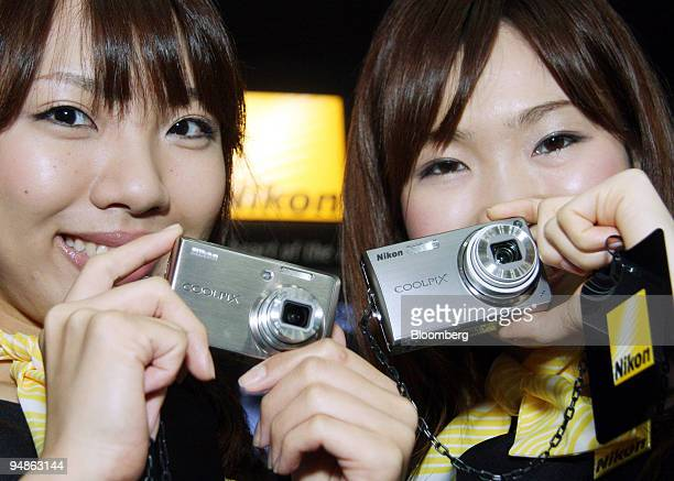 Models show off Nikon Corp's Coolpix S600 left and Coolpix S550 digital cameras at the Photo Imaging Expo in Tokyo Japan on Wednesday March 19 2008...