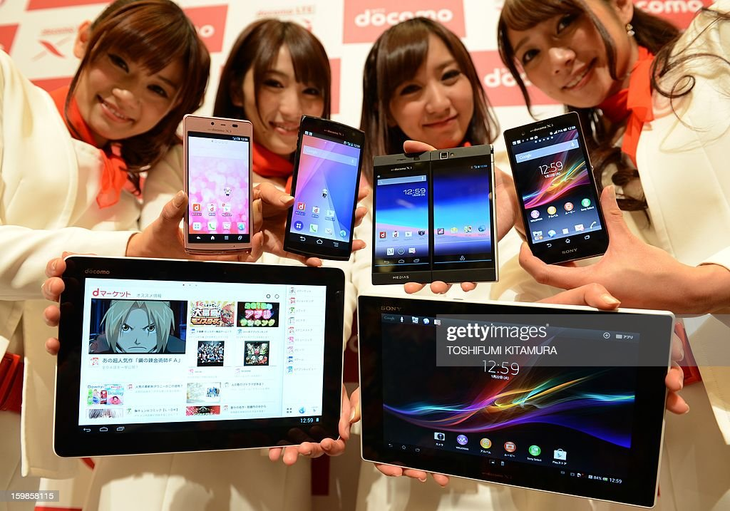 Models show off NTT Docomo's new smartphones (top from L; Aquos Phone EX, Arrows X, Medias W and Xperia Z) and tablets (lower from L; Xperia Tablet Z and 'dtab') during the company's 2013 Spring lineup press preview in Tokyo on January 22, 2013. The new lineup of 11 smartphones and tablets plus one mobile Wi-Fi router will launch in sequence beginning on January 25 in Japan.