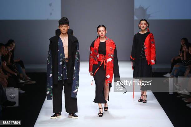 Models showcase designs designed by graduates of College of Fine Arts of University of Jinan on the runway during day one of China Graduate Fashion...