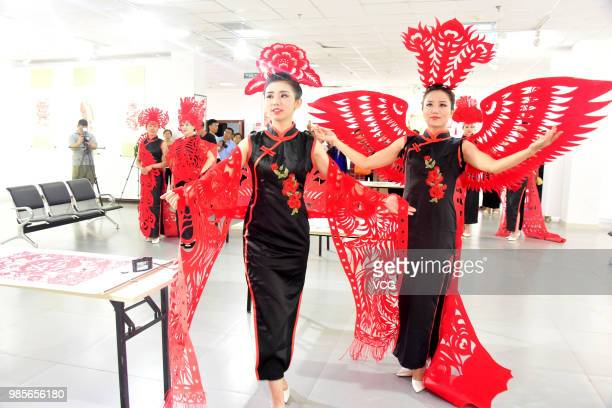 Models showcase papercutting designs during a traditional Chinese papercutting skill show on June 25 2018 in Chiping County Shandong Province of China