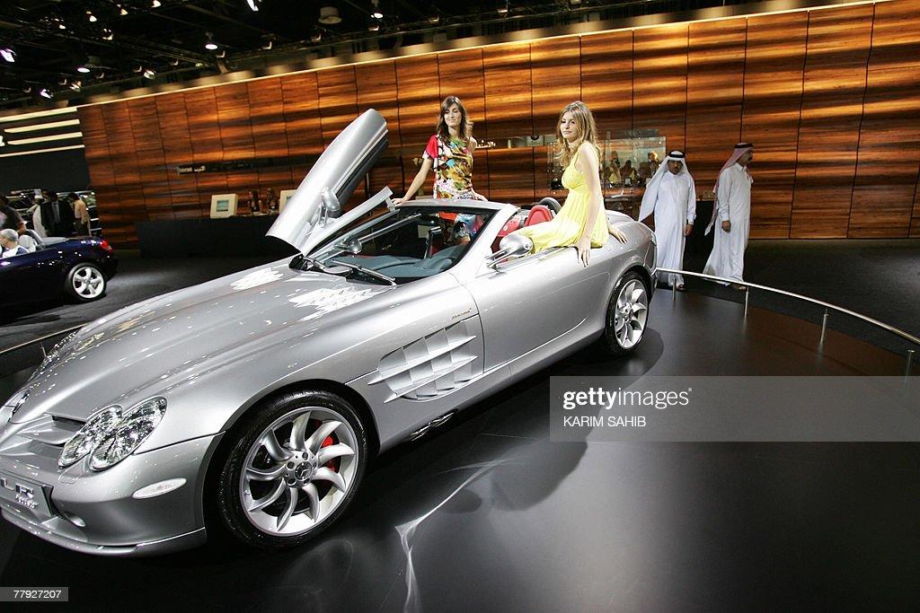 Models Sit On A New Mercedes Benz SLR McLaren Roadster Open Top Sports Car