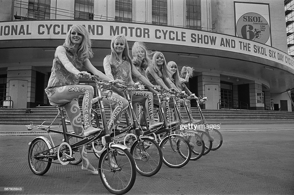 Models sit on Moulton bicycles outside the 'National Cycle