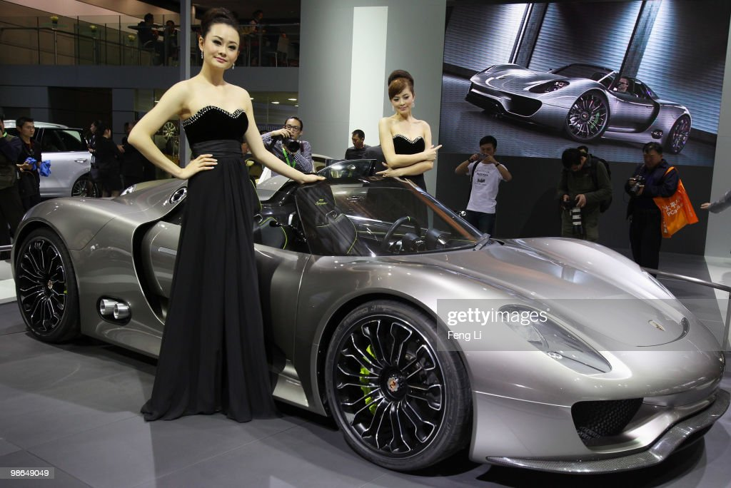 Models stand beside the Porsche 918 Spyder concept car during a special media opening of the Beijing Auto Show on April 24, 2010 in Beijing of China. Major global automakers plan to unveil dozens of new models at the Beijing auto show, which has quickly become one of the biggest and most important auto shows in the world and raises its curtains on Friday and will last till May 2, during which 990 models - with 89 making their global debut - will be displayed in a 200,000-sq-m area.