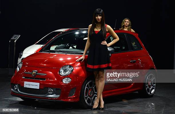 Models stand near the Abarth 595 Competizione car at the Indian Auto Expo 2016 in Greater Noida some 45kms east of New Delhi on February 4 2016...