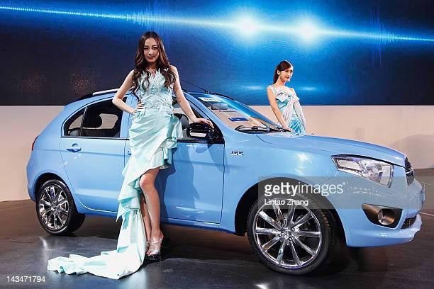 Models stands beside a Reiz R008 car is displayed during the 2012 Beijing International Automotive Exhibition at beijng International Exhibition...