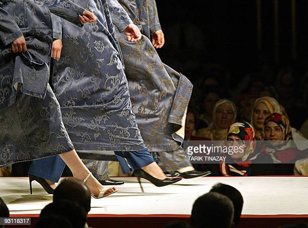 Models stroll down a catwalk in Islamic attire during a fashion show03 June 2003 which was moved to an Ankara hotel from its original venue a former...