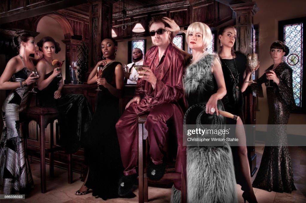 Models surrounding powerful man in pajamas at party : Stock Photo