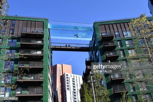 Models swim in a transparent acrylic swimming pool bridge that is fixed between two apartment blocks at Embassy Gardens next to the new US Embassy in...