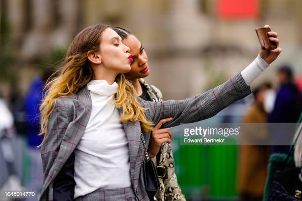 Models take a selfie outside Chanel during Paris Fashion Week Womenswear Spring/Summer 2019 on October 2 2018 in Paris France