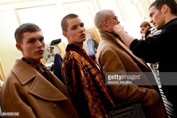 Models wait backstage before for fashion house Versace during the Men's Fall/Winter 2019 fashion shows in Milan on January 13 2018 / AFP PHOTO /...
