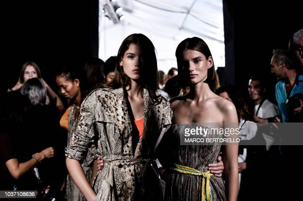 A model checks her mobile phone as she waits in the backstage prior to the presentation of the Blumarine fashion house during the Women's...
