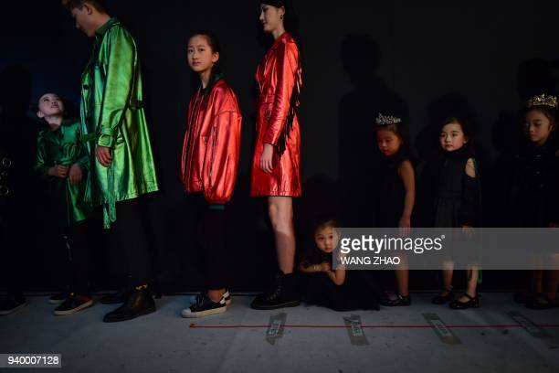 Models wait to present creations from the Sun Haitao collection during China Fashion Week in Beijing on March 30 2018 / AFP PHOTO / WANG ZHAO