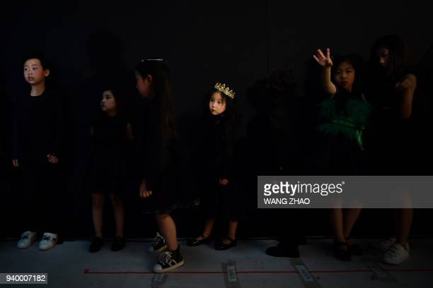 TOPSHOT Models wait to present creations from the Sun Haitao collection during China Fashion Week in Beijing on March 30 2018 / AFP PHOTO / WANG ZHAO
