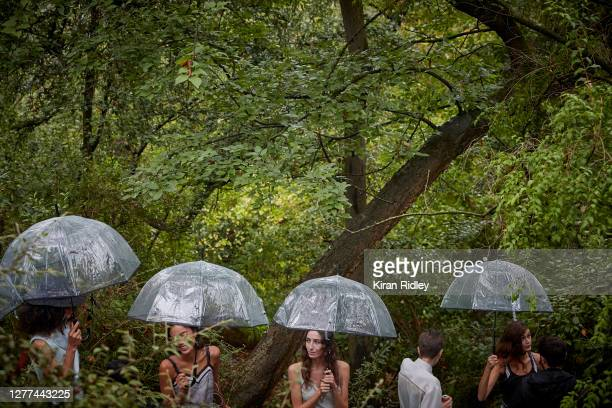 Models wait under umbrellas backstage at the Koche Womenswear Spring/Summer 2021 show in the Jardin des Buttes Chaumont on the first day of Paris...