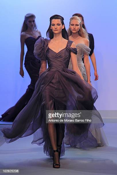 Models walk down the catwalk during the Christophe Josse show as part of the Paris Haute Couture Fashion Week Fall/Winter 2011 at Palais De Tokyo on...