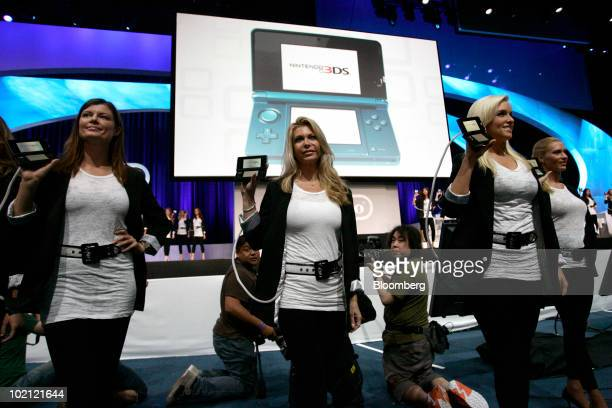 Models walk on stage with Nintendo Co's new 3DS game at the Electronic Entertainment Expo in Los Angeles California US on Tuesday June 15 2010...