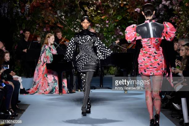 Models walk the runway as Freya Ridings performs at the Richard Quinn show during London Fashion Week February 2019 at Ambika P3 on February 19, 2019...