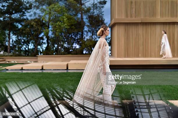 Models walk the runway as the dome of the Gand Palais is reflected in the phone screen during the Chanel Spring Summer 2016/2017 show on January 26...