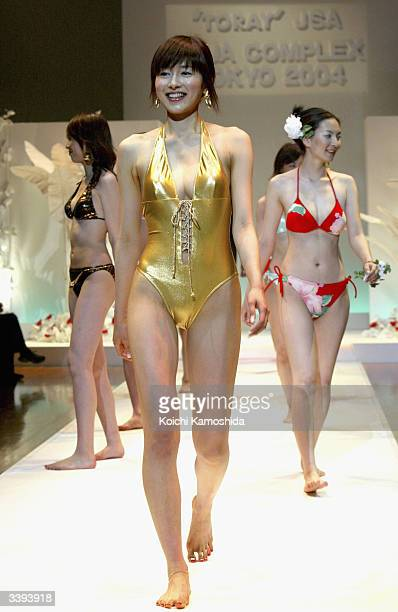 Models walk the runway during Toray's fashion show for the summer 2004 'Aqua Complex Tokyo 2004' on April 16 2004 in Tokyo Japan Toray uses their...