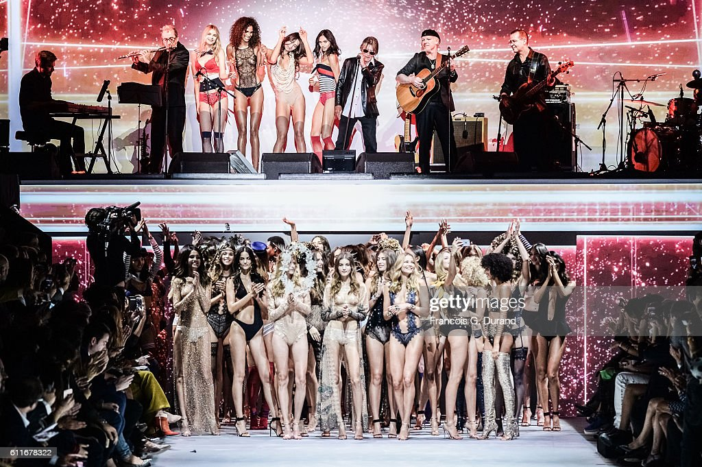 . Models walk the runway while singer Jacques Dutronc performs on stage during the Etam show as part of the Paris Fashion Week Womenswear Spring/Summer 2017 on September 27, 2016 in Paris, France.