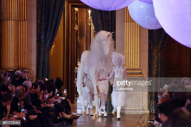 Models walk the runway with unicorn puppet at the Thom Browne Spring Summer 2018 fashion show during Paris Fashion Week on October 3 2017 in Paris...