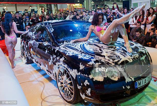 Models wash a car in swimsuit during a threeday auto motor and tuning show at the Hungexpo Budapest Fair Center in Budapest on March 18 2016 / AFP /