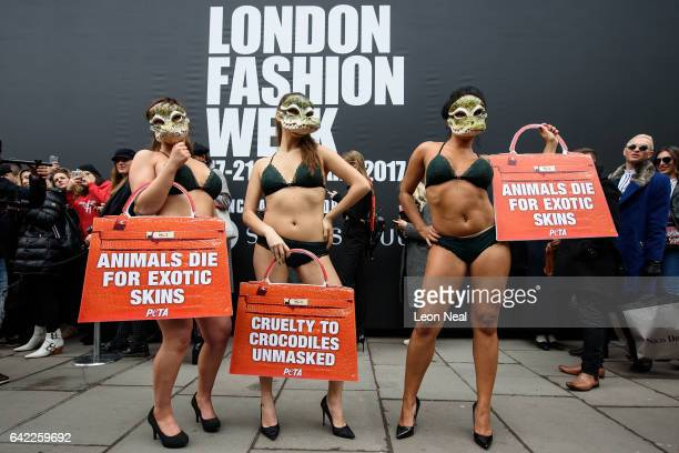 Models weaering lingerie and crocodile masks take part in a protest for the PETA animal welfare group outside the London Fashion Week venue on...