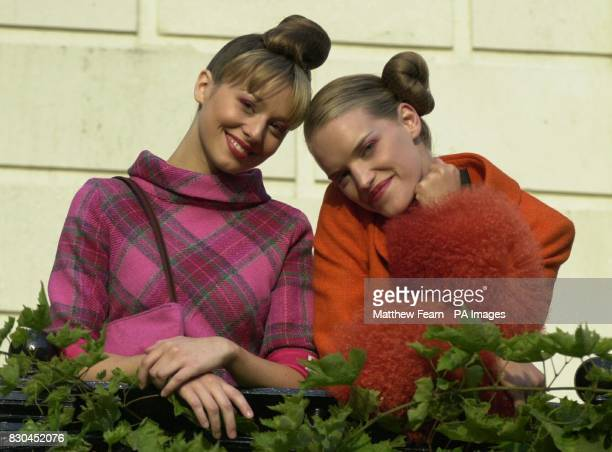 Models wear a pink check Harris Tweed dress by Susy Harper and an orange Harris Tweed jacket with mockfur cuffs by Bruce Oldfield during a reception...