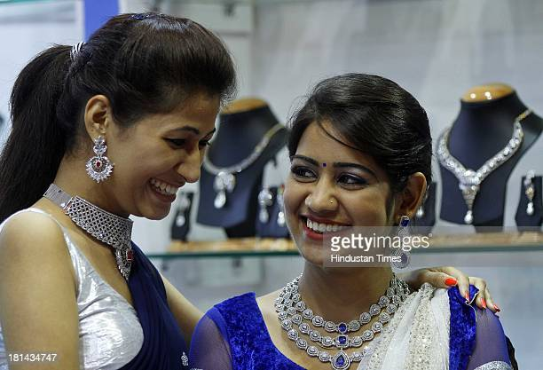 Models wear diamond necklace and earrings at a jewellery stand at the global B2B Jewellery and Gem Fair 2013 at Pragati Maidan on September 21 2013...