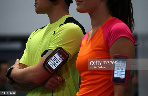 Models wear smartphones that collect fitness data from the Casio STB1000 bluetooth enabled watch in the Casio booth at the 2014 International CES at...
