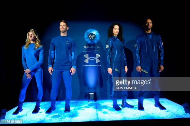 Models wear Virgin Galactic's new space-wear system, developed in partnership with Under Armour, during an event to unveil the suits to be worn by...