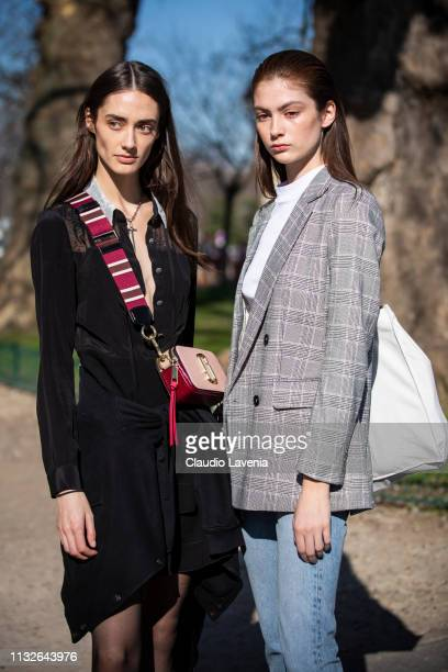 Models wearing a black dress and Marc Jacobs bag and white top checked blazer blue denim jeans and white bag are seen outside Unravel Project on Day...