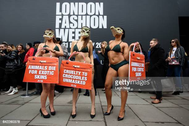 Models wearing lingerie and crocodile masks take part in a protest for the PETA animal welfare group outside the London Fashion Week venue on...
