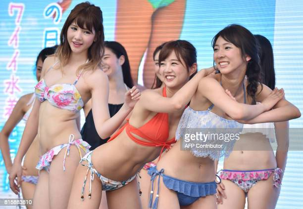Models wearing new bikinis pose for the media following a promotional flash mob dance performance in Tokyo on July 17 2017 The event was organized by...