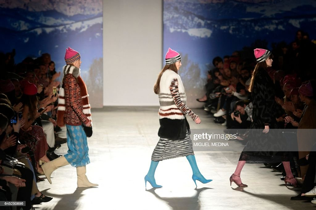 Models wearing pink hats walk the runway at the end of the show for fashion house Missoni during the Women's Fall/Winter 2017/2018 fashion week in Milan, on February 25, 2017. Italian designer Angela Missoni brought the political fight to Milan fashion week by ending her autumn-winter 2017 show with models clad in Pussyhats, the pink protest symbols of women's rights. / AFP PHOTO / Miguel MEDINA