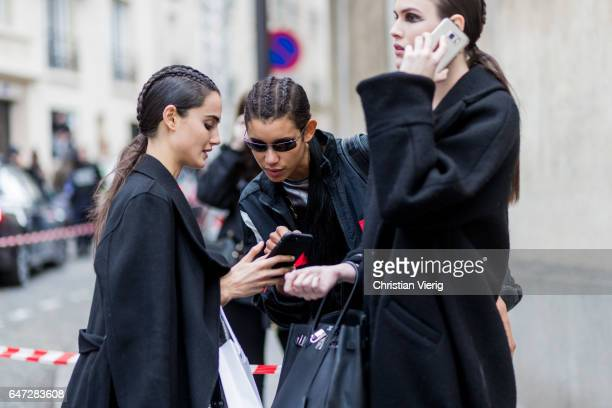 Models with braids searching for the way on their phone outside Balmain on March 2 2017 in Paris France