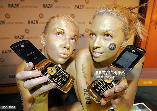 Models with their bodies painted in gold show Motorola's new cell phones Razr2 Luxury Edition during a sale promotion event in Seoul on February 28...
