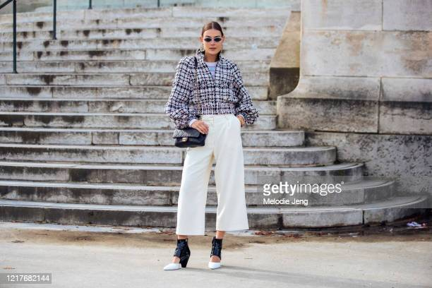 Model/Stylist Vera van Erp attends the Chanel show in earrings, a black and white tweed jacket, Chanel sweater, gold bracelet, black quilted Chanel...