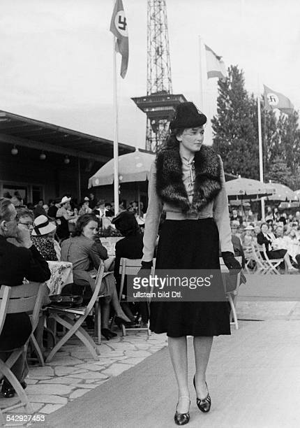 Modenschau am Funkturm in Berlin: ein Mannequin führt ein Nachmittagskleid mit schwarzem Glockenrock, grauer Wolljacke und Silberfuchs vor, im...