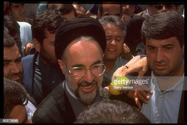 Moderate cleric presidential candidate Mohammed Khatami , surprise front-runner, in crowd of supporters outside polling station on election day.