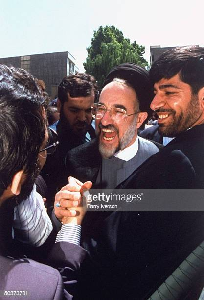 Moderate cleric presidential candidate Mohammed Khatami , surprise front-runner, shaking hands in crowd of supporters outside polling station on...