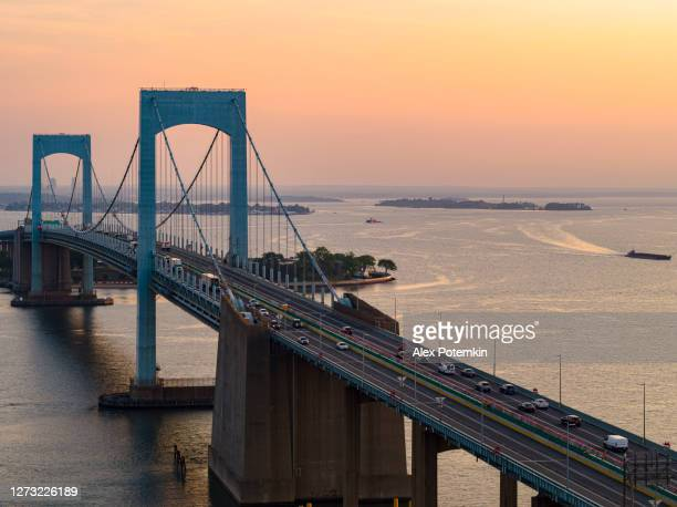 moderate traffic on throgs neck bridge over east river connecting queens and bronx boroughs, new york, at sunrise. - bronx stock pictures, royalty-free photos & images