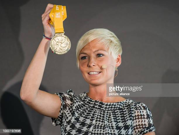 Moderator Anett Sattler holds the event's gold medal during the final draw for the 2017 World Women's Handball Championship which took place in...