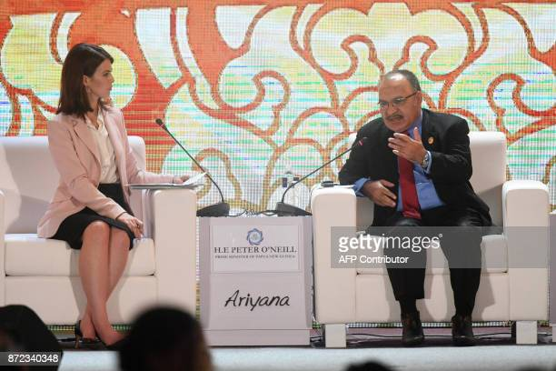 Moderator Nancy Hungerford of CNBC looks on as Papua New Guinea's Prime Minister Peter O'Neill speaks during a dialogue on the final day of the APEC...