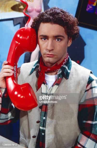 Moderator Thomas Tommy Krappweis mit übergroßem Telefon im Studio von Disney TV bei RTL in Köln, Deutschland 1994. .