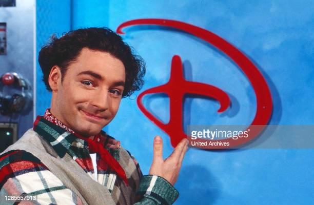 Moderator Thomas Tommy Krappweis mit dem Logo im Studio von Disney TV bei RTL in Köln, Deutschland 1994. .