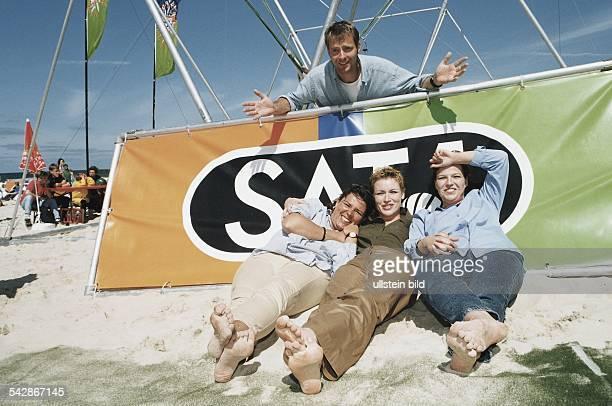 Moderator und Moderatoinnen des Privatsenders SAT1 am Strand von Westerland Jörg Pilawa hängt mit präsentierender Geste über einer SAT1 Plane Davor...